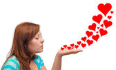 Young woman blowing hearts — Stock Photo