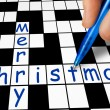 Stock Photo: Hand filling in crossword - Merry Christmas