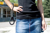 Woman in mini skirt holding handcuffs. — Foto de Stock