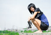 Young woman sitting on top of a stone — Stock Photo