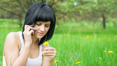 Girl with dandelion talking on mobile — Stock Photo