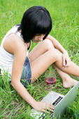 Young girl sitting in a park with laptop computer — Stock Photo