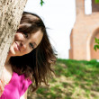 Beautiful young woman hiding behind a tree — Stock Photo