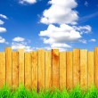 Wooden fence with green grass and field — Stock Photo