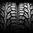 Winter car tyre on a black background — Stock Photo