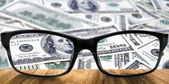 Clear dollar in glasses — Stock Photo
