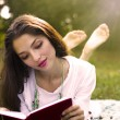Nice young woman lies on green grass and reads a book — Stock Photo
