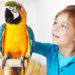 Child with ara parrot — Stock Photo #14123185