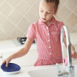 Little girl washing the dishes - Stock Photo