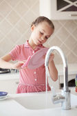 Little girl washing the dishes — Stok fotoğraf