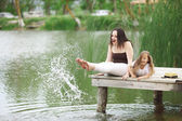Family resting near pond — Stock Photo