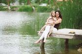 Family resting near pond — Stock Photo