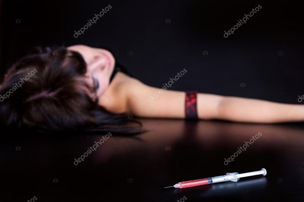 Drug addict woman with syringe is sleeping on table. Simulated, studio shot. Focus is on the syringe  Stock Photo #13706562