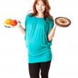 A pregnant smiling woman is holding food in her hands — Stock Photo #13912304