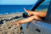Woman's legs in a car window — Stock Photo