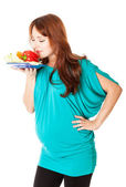 A pregnant woman with a plate of vegetables — Stockfoto