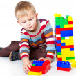 Stock Photo: A funny boy is playing with lego