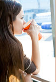 Woman is drinking coffee in airport — Stock Photo