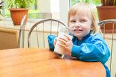 Little funny girl is drinking milk — Stock Photo