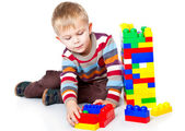 A funny boy is playing with lego — Stock Photo