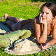 Woman in swimsuit is lying on green grass near the sea — Stock Photo