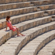 Girl is sitting on the steps of amphitheater - Zdjęcie stockowe