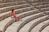 Girl is sitting on the steps of amphitheater — Stock Photo