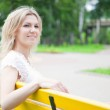 Woman is sitting on the yellow bench in the park — Stock Photo #7714483