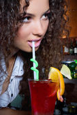 Brunette girl  with coctail in bar — Stock Photo