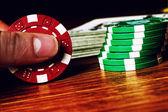 Gambling chips between fingers — Stock Photo