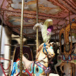 Horse rides on merry-go-round carousel — Stock Photo #30340075