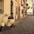 Vintage scooter parked in a typical narrow old street in Rimini, Italy — Stock Photo #37970831