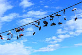 Old Shoes hanging on electrical wire against a blue sky — Foto de Stock
