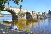 Unidentified wedding couple on the waterside of the Vltava River near Charles Bridge in Prague, Czech Republic. — Stock Photo
