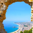 View of Spanish beach through a stone door of the St. John Castle of resort town Blanes in summertime. Costa Brava, Catalonia, Spain — Stock Photo #40547155
