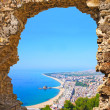 View of Spanish beach through a stone door of the St. John Castle of resort town Blanes in summertime. Costa Brava, Catalonia, Spain — Stock Photo #40804129