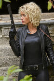 Woman in leather with silencer gun — Stock Photo