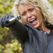 Screaming woman shooting from handgun — Stock Photo