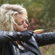 Woman shooting with bow and arrow — Stock Photo