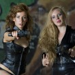 Two leather clad gun girls — Stock Photo