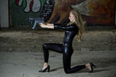 Gun woman in leather catsuit — Stock Photo