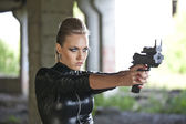 Woman with gun in leather suit — Stock Photo