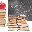 Back to School written on a blackboard with books and red apple — Stock Photo