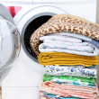 A washing machine and a big pile of laundry - ストック写真
