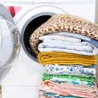 A washing machine and a big pile of laundry - Stockfoto