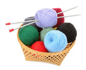 Balls of yarn in a basket with knitting needles — Stock Photo