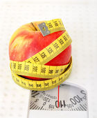 Measuring tape and apple on scales — Stock Photo