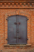 Historical old closed metal window shutter in brick wall — Stock Photo