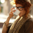 Royalty-Free Stock Photo: Hipster girl drinking coffee outdoors