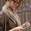 Hipster girl listening to music on mp3 player — Stock Photo